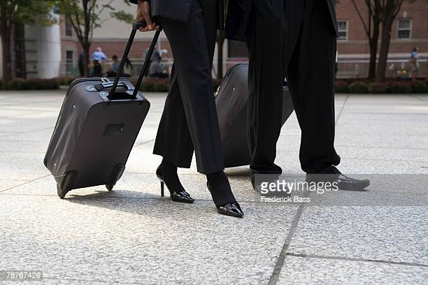 Businessman and businesswoman pulling luggage in the city