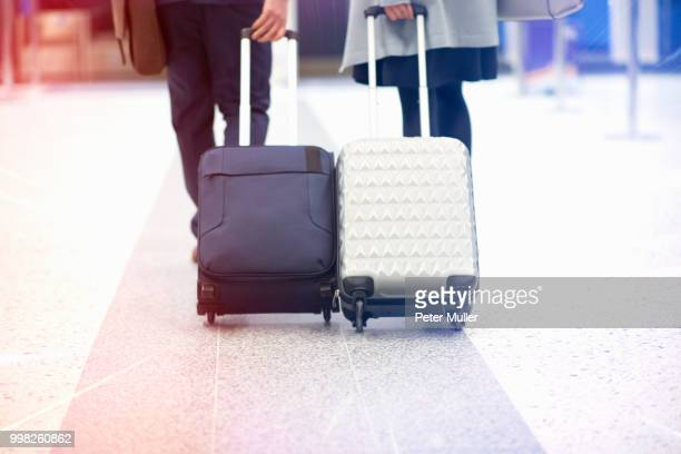 Businessman and businesswoman pulling wheeled suitcases, low section, rear view
