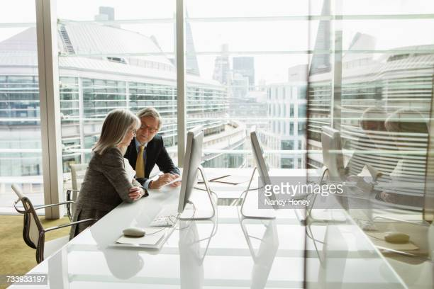 businessman and businesswoman reading and analysing report, london, uk - 法律関係の職業 ストックフォトと画像