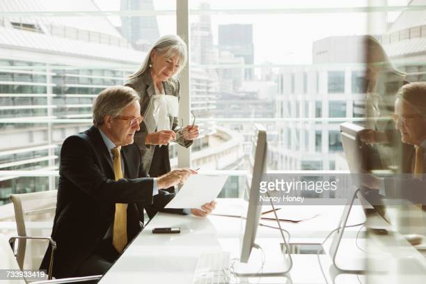 businessman and businesswoman reading and analysing report, london, uk - law office stock photos and pictures