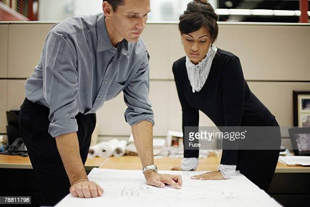 Businessman and Businesswoman Reading Blueprint