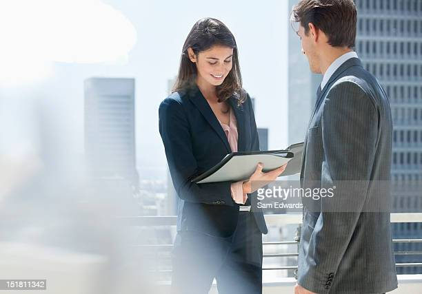 Businessman and businesswoman reviewing paperwork on urban balcony