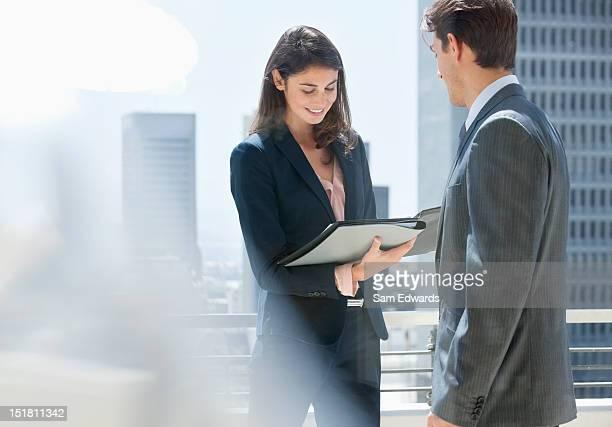 Homme d'affaires et Femme d'affaires examinant des documents sur urban balcon