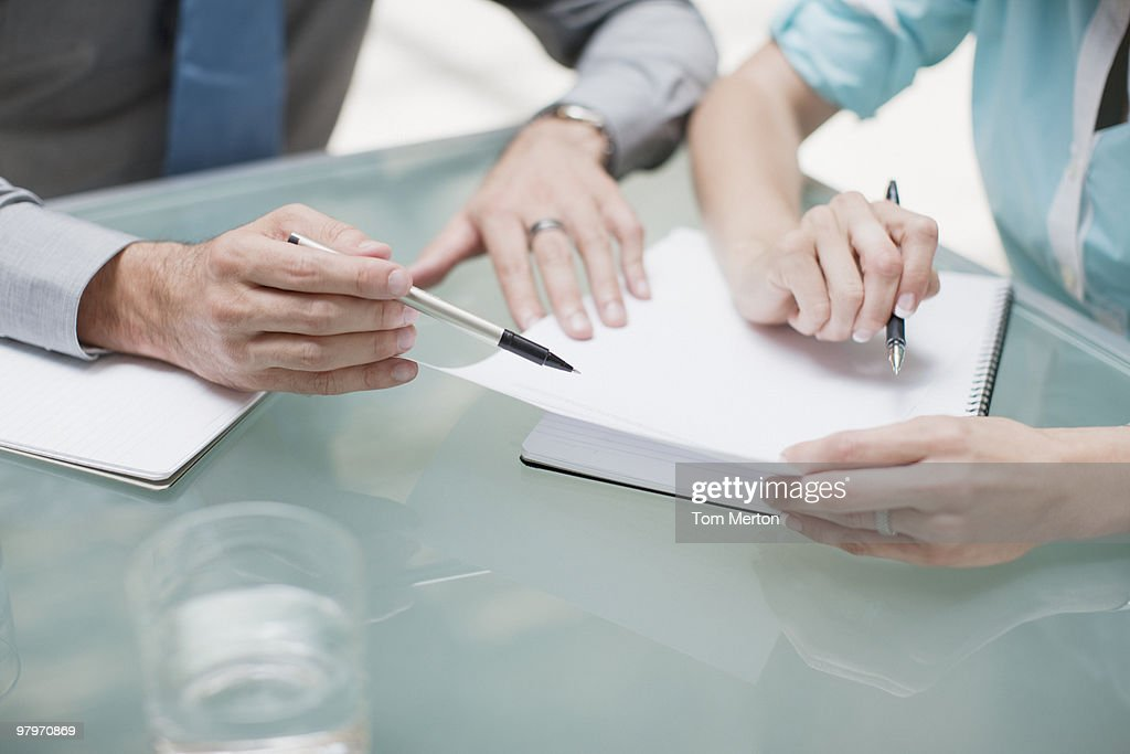 Businessman and businesswoman reviewing paperwork : Stock Photo