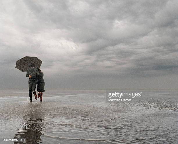 Businessman and businesswoman running in rain with umbrella, rear view