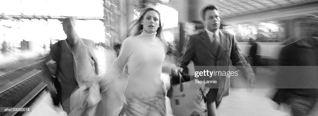 Businessman and businesswoman running on train platform, blurred, B&W : Stockfoto