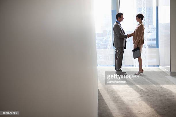 Businessman and businesswoman shaking hand in lobby