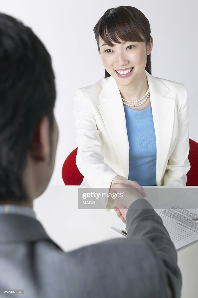 Businessman and Businesswoman Shaking Hands Across a Table : Stock Photo