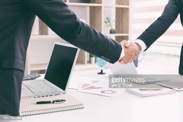 businessman businesswoman shaking hands after meeting