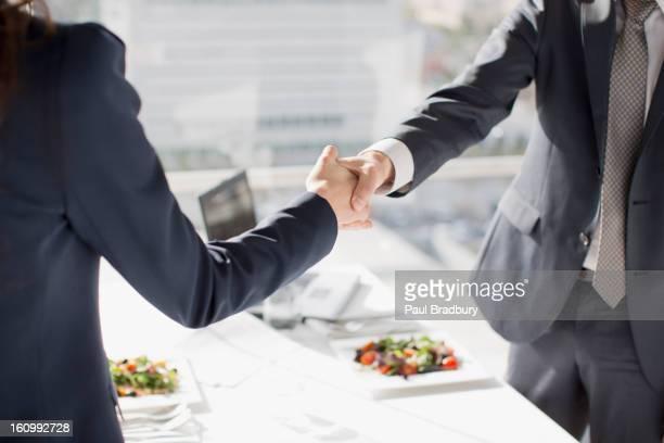 ビジネスマンやビジネスウーマンの手を振るテーブルでの昼食