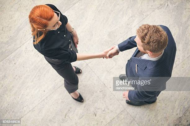 Businessman and businesswoman shaking hands in the lobby overhea