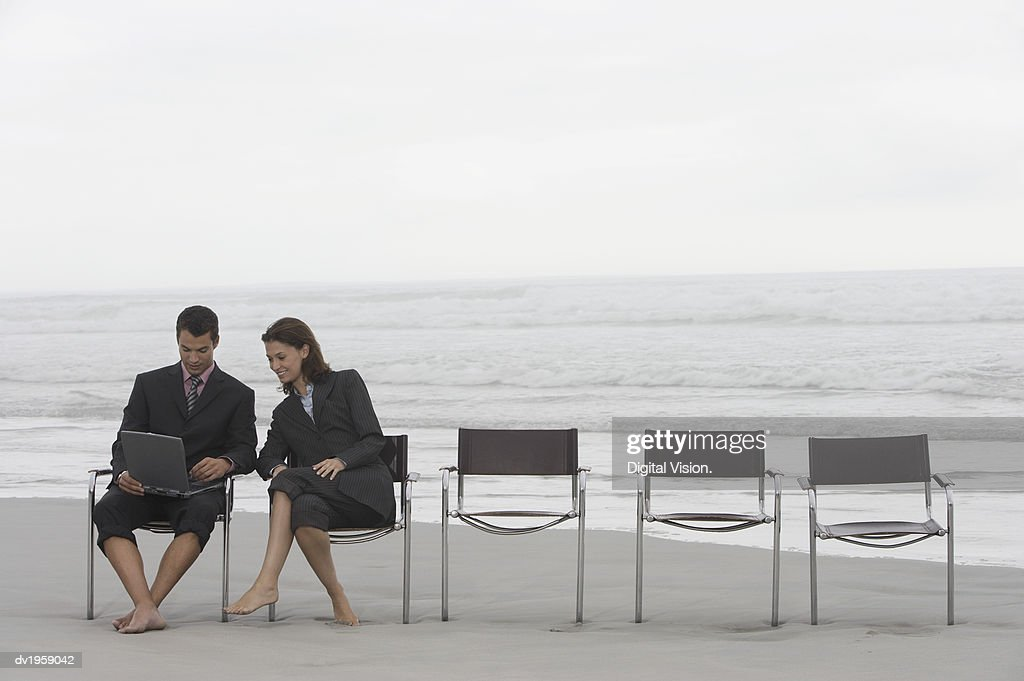 Businessman and Businesswoman Sit at the End of a Row of Chairs on a Beach, Using a Laptop : Stock Photo