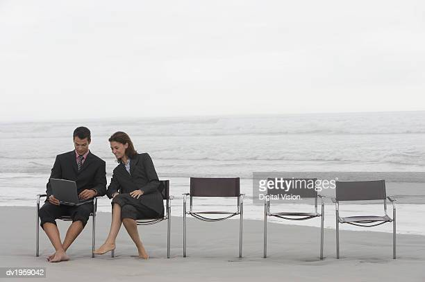 businessman and businesswoman sit at the end of a row of chairs on a beach, using a laptop - side by side stock photos and pictures