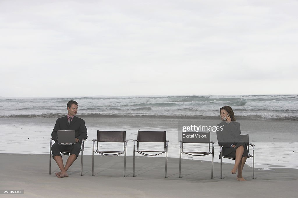 Businessman and Businesswoman Sit at the Ends of a Row of Chairs on a Beach, Using a Laptop and Talking on a Mobile Phone : Stock Photo