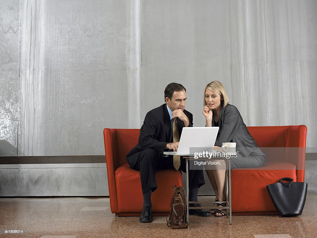 Businessman and Businesswoman Sit in Armchairs in a Lobby, Using a Laptop and Talking : Stock Photo