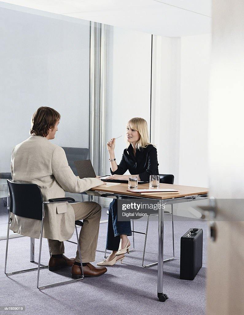 Businessman and Businesswoman Sit Opposite Each Other at a Table in an Office, Having a Discussion : Stock Photo