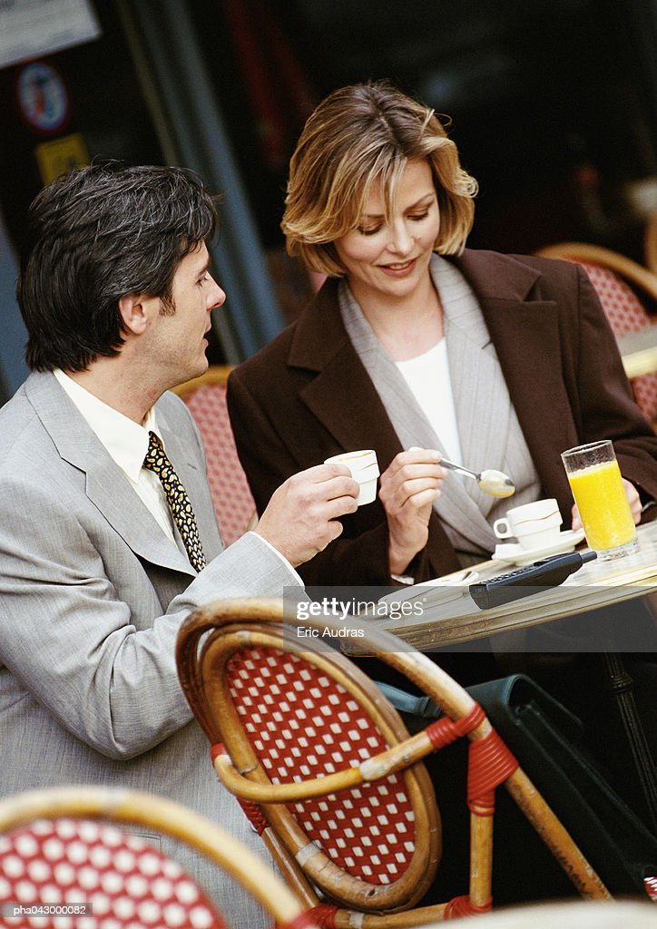 Businessman and businesswoman sitting at cafe terrace : Stockfoto