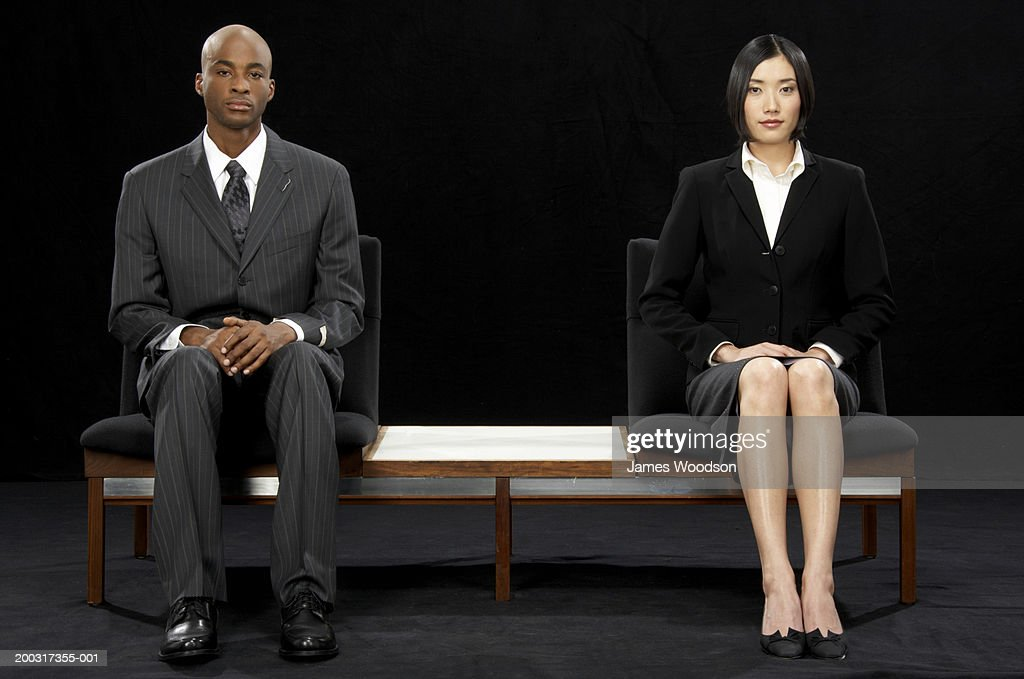 Businessman and businesswoman sitting at opposite ends of bench : Stock Photo