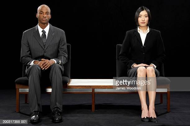 businessman and businesswoman sitting at opposite ends of bench - zij aan zij stockfoto's en -beelden