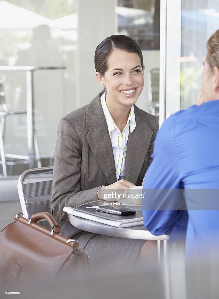 Businessman and businesswoman sitting at outdoor patio table : Stock Photo