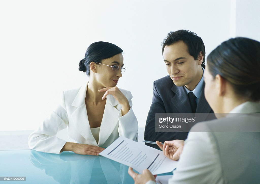 Businessman and businesswoman sitting at table across from businesswoman holding out document and pen : Stock Photo