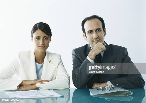 Businessman and businesswoman sitting at table with documents