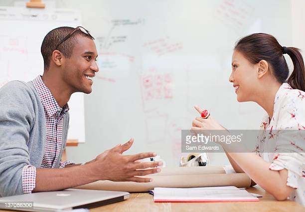 businessman and businesswoman sitting face to face in meeting - gesturing stock pictures, royalty-free photos & images