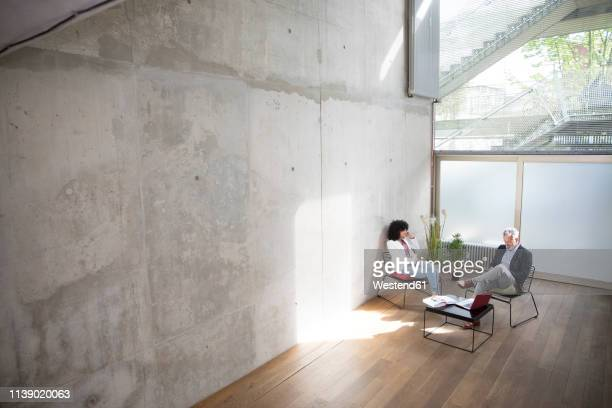 businessman and businesswoman sitting in a loft at concrete wall - natural phenomena stock pictures, royalty-free photos & images