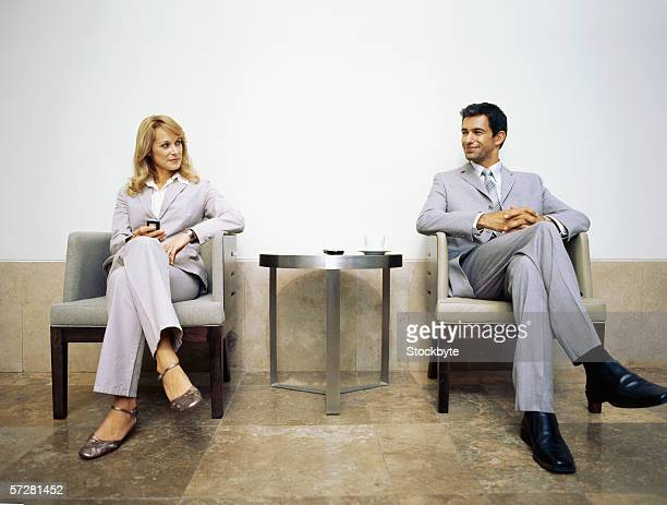 Businessman and businesswoman sitting on armchairs