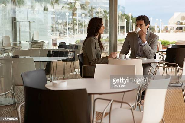 Businessman and businesswoman sitting outside Cafe drinking coffee. Alicante, Spain.