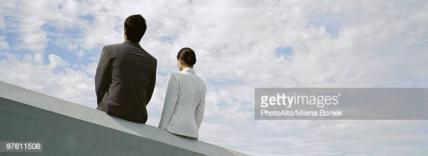 Businessman and businesswoman sitting side by side on rooftop ledge