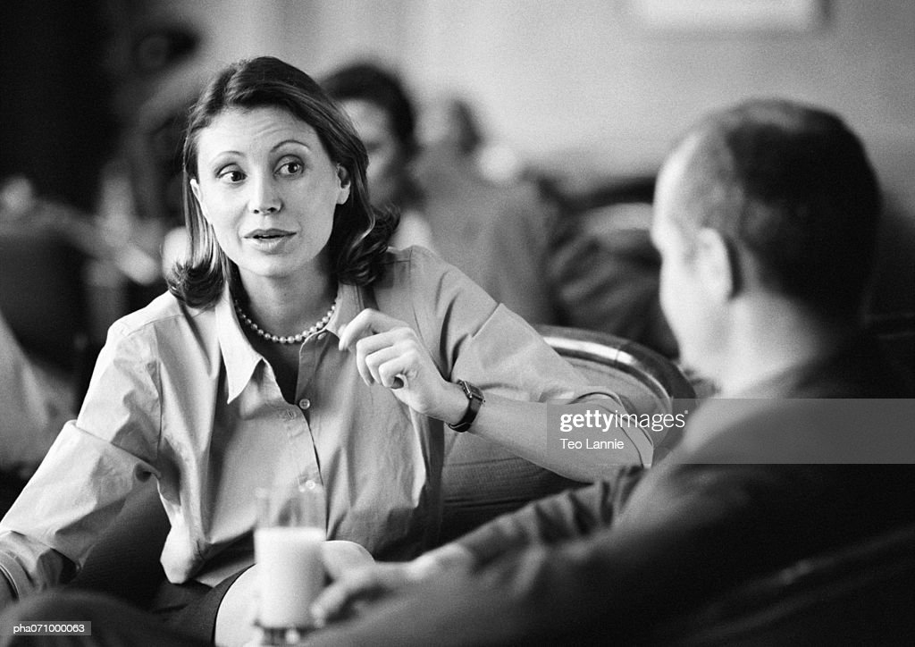 Businessman and businesswoman sitting together talking, b&w. : Stockfoto