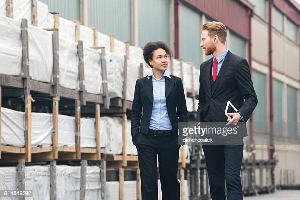 Businessman and businesswoman speaking near storage