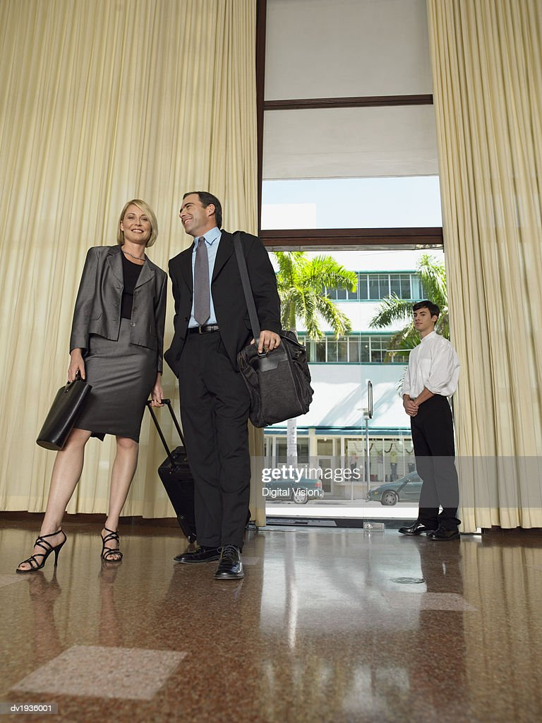 Businessman and Businesswoman Stand in a Hotel Lobby Carrying Luggage : Stock Photo