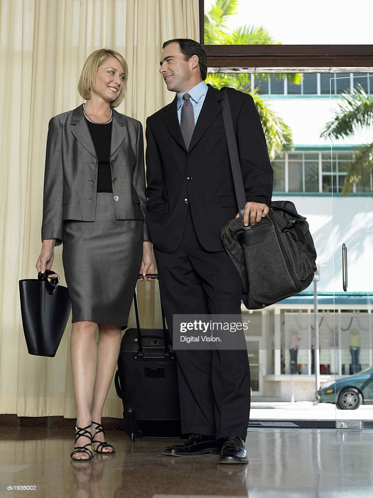 Businessman and Businesswoman Stand in a Hotel Lobby Carrying Luggage and Talking to Each Other : Stock Photo