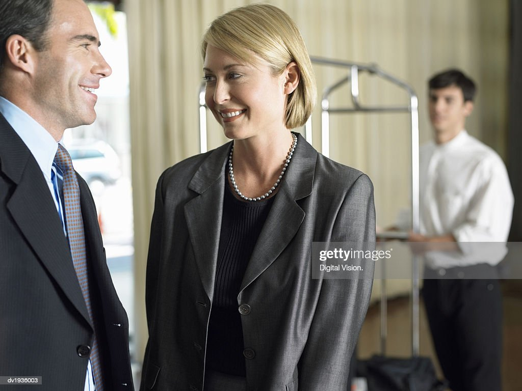 Businessman and Businesswoman Stand Talking to Each Other, a Hotel Porter in the Background : Stock Photo