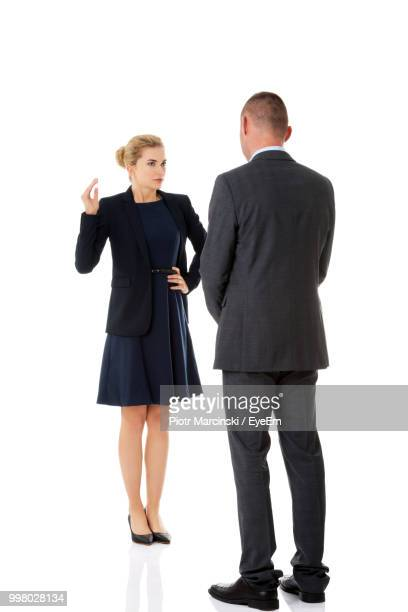 Businessman And Businesswoman Standing Against White Background