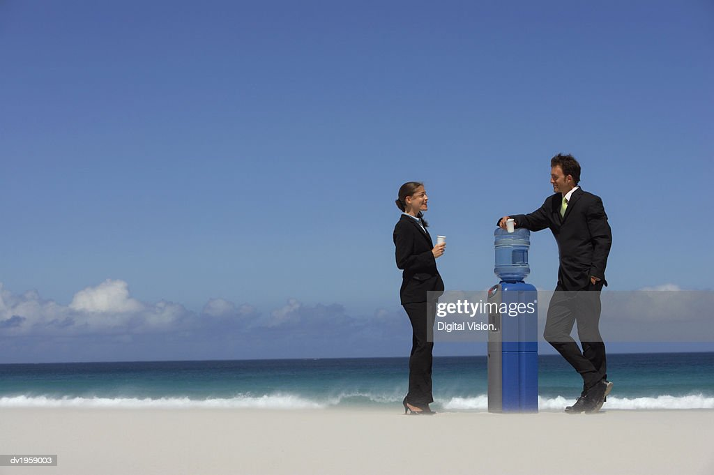 Businessman and Businesswoman Standing and Taking By a Water Cooler on a Beach : Stock Photo