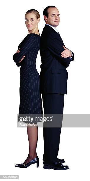Businessman and businesswoman standing back to back