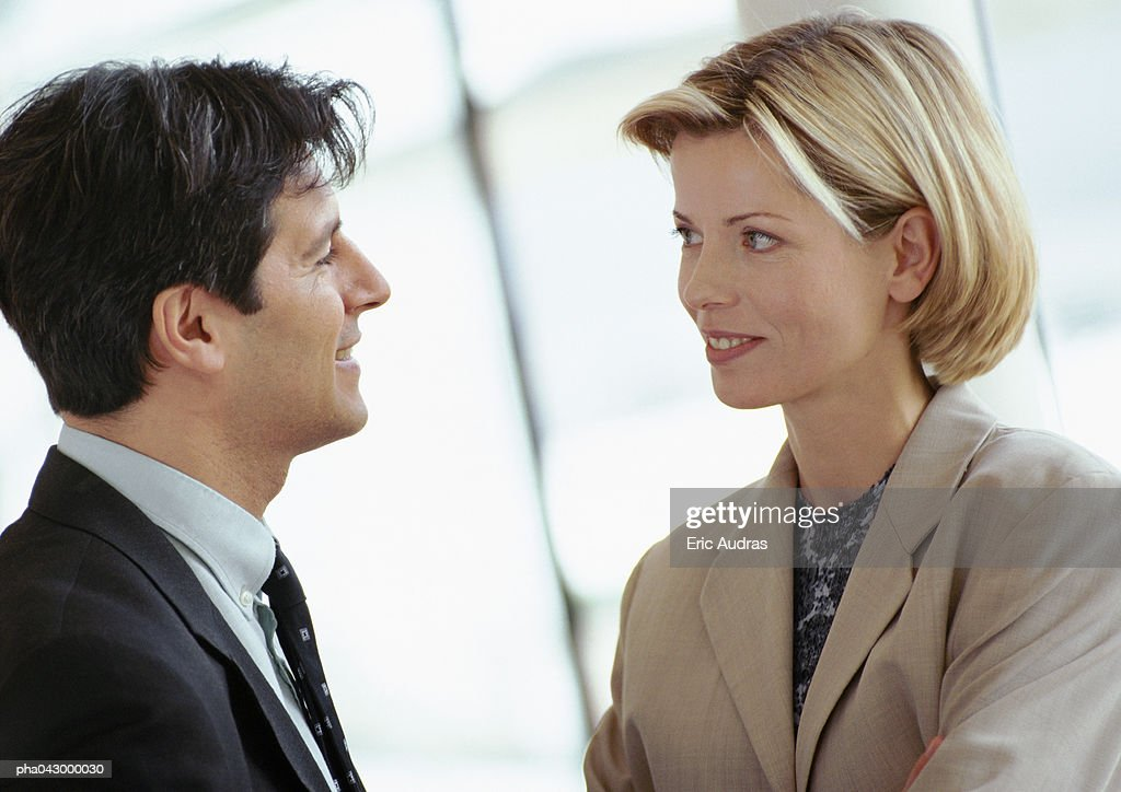 Businessman and businesswoman standing face to face, close-up : Stockfoto