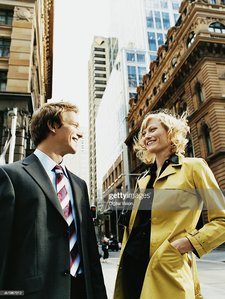Businessman and Businesswoman Standing Face to Face in the City and Smiling : Stock Photo