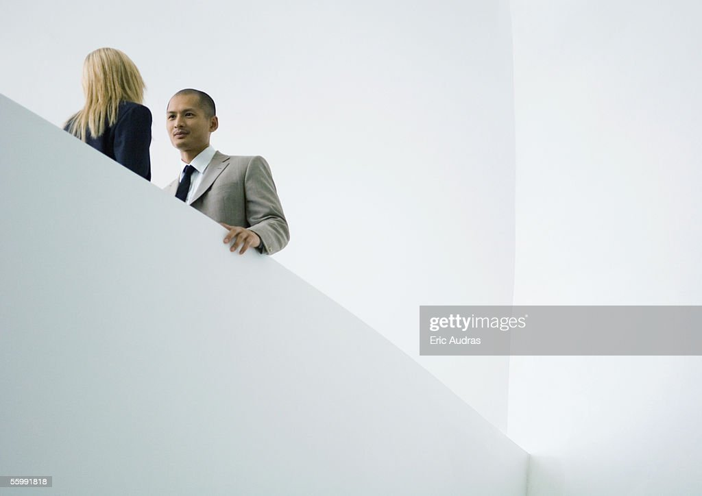 Businessman and businesswoman standing face to face, low angle view : Stock Photo