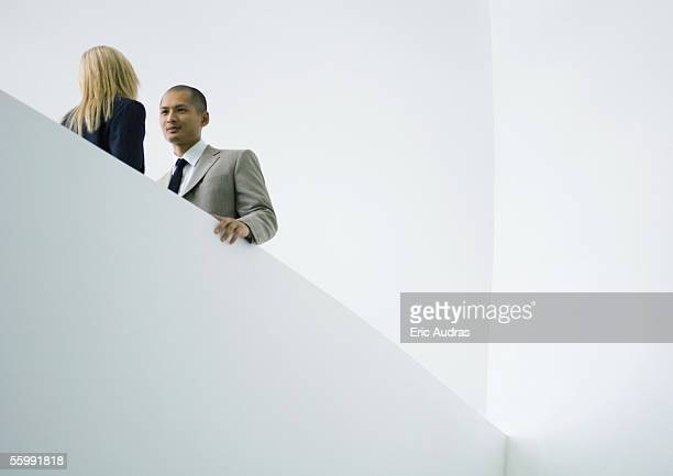 Businessman and businesswoman standing face to face, low angle view