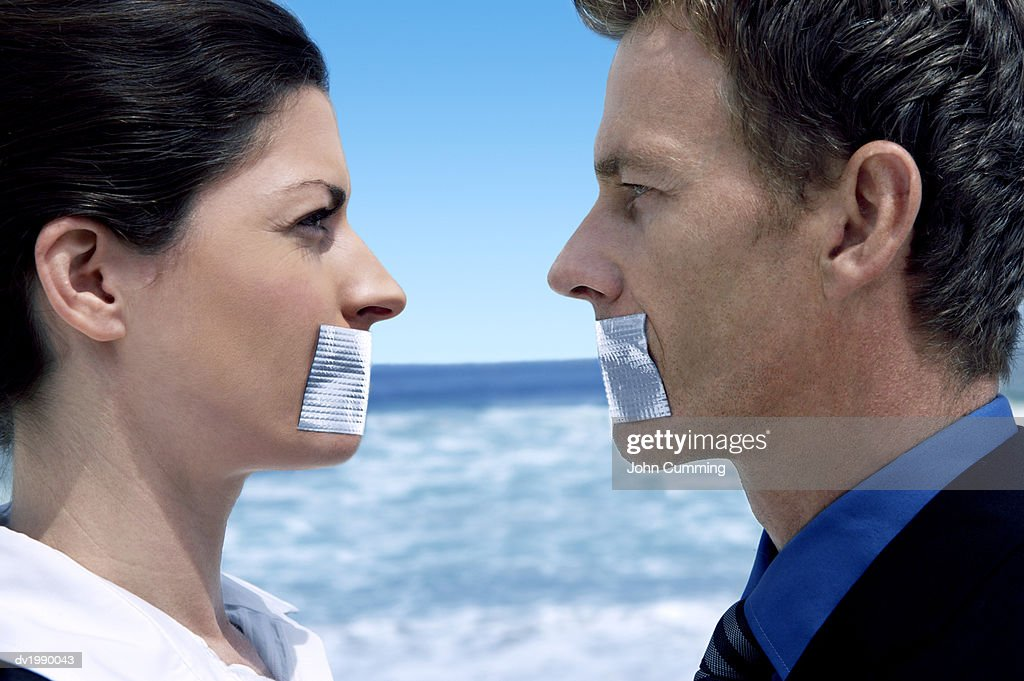 Businessman and Businesswoman Standing Face to Face on a Beach With Their Mouths Covered in Duct Tape : Stock Photo