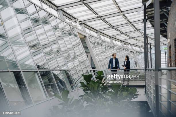 businessman and businesswoman standing on a skywalk in modern office building - architektur stock-fotos und bilder