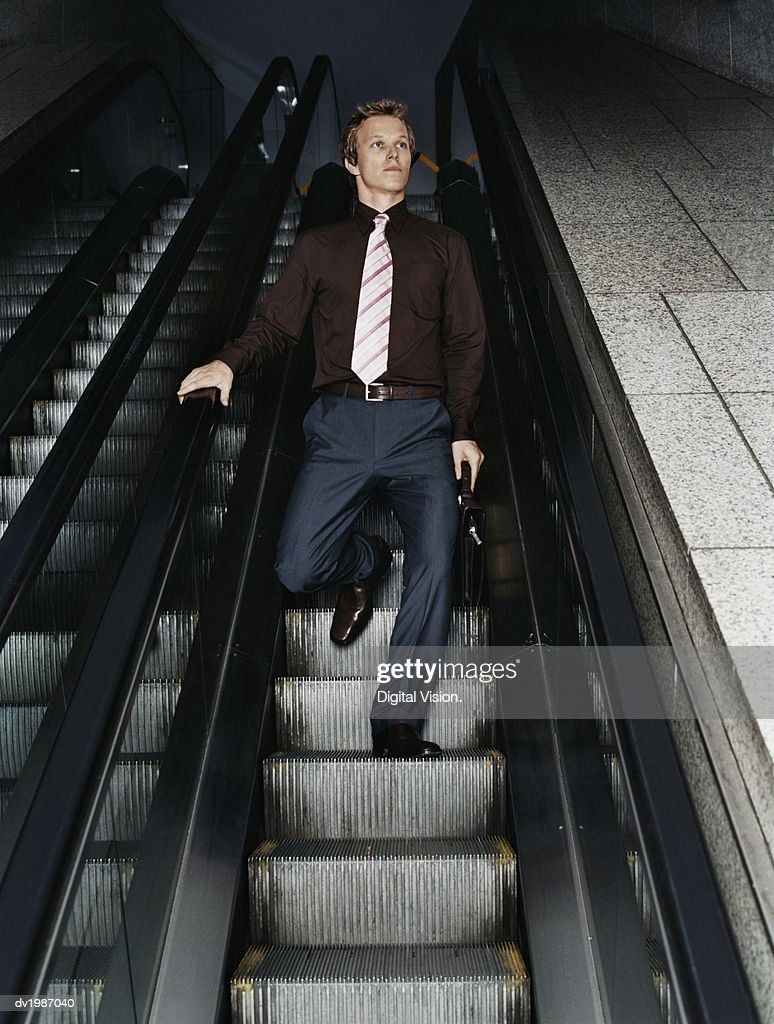 Businessman and Businesswoman Standing on an Elevator : Stock Photo