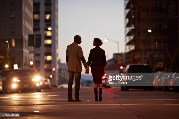 Businessman and businesswoman standing on San Francisco street and holding hands at night