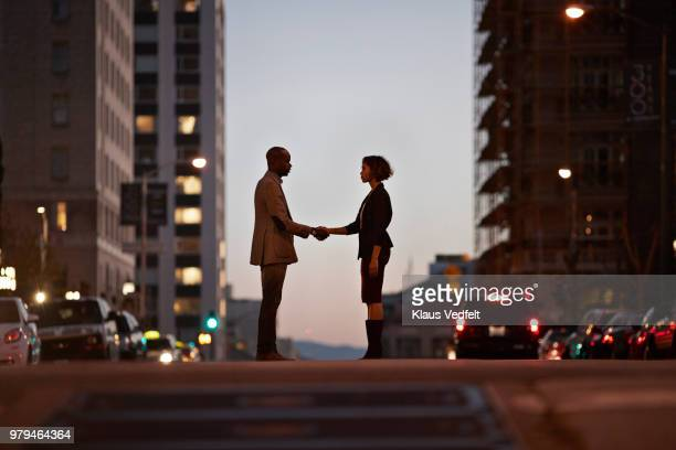Businessman and businesswoman standing on San Francisco street and making handshake at night