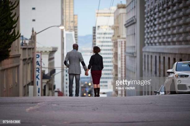 Businessman and businesswoman standing on top of steep San Francisco street and holding hands