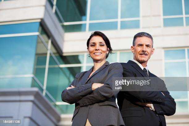 Businessman and businesswoman standing outside office building
